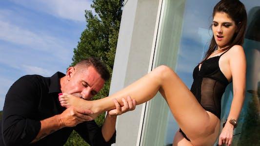A man kisses a woman's foot seductively