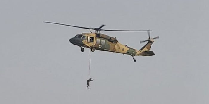 a human figure suspended under a helicopter