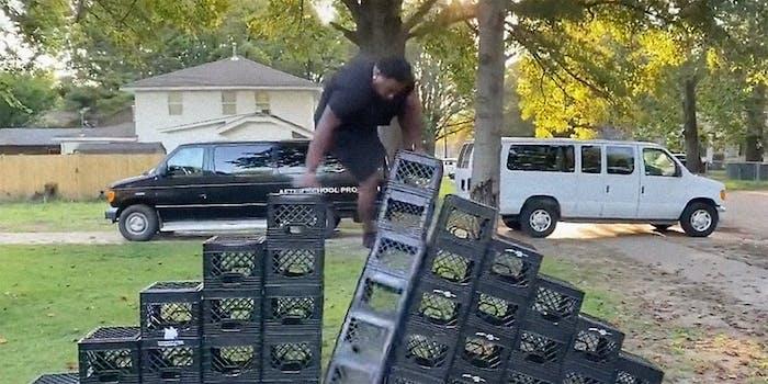 A man climbing a pile of milk crates.