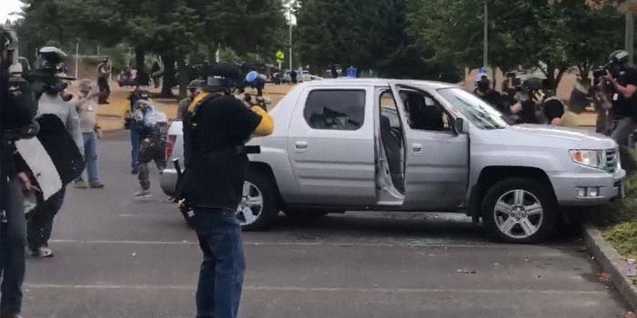 men in proud boys shirts fire paintball guns at man in truck as others attack him from the driver's side window