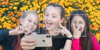 Three girls making faces at iPhone with facial recognition squares on their heads