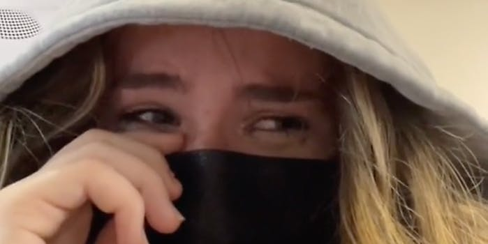 A woman crying with a mask on.