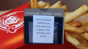 """Wendy's fries with inset of drive-thru window covered by sign that reads """"Sorry I'm short staffed I can only make fry's, nuggets, chili, potatoes, and drinks."""""""