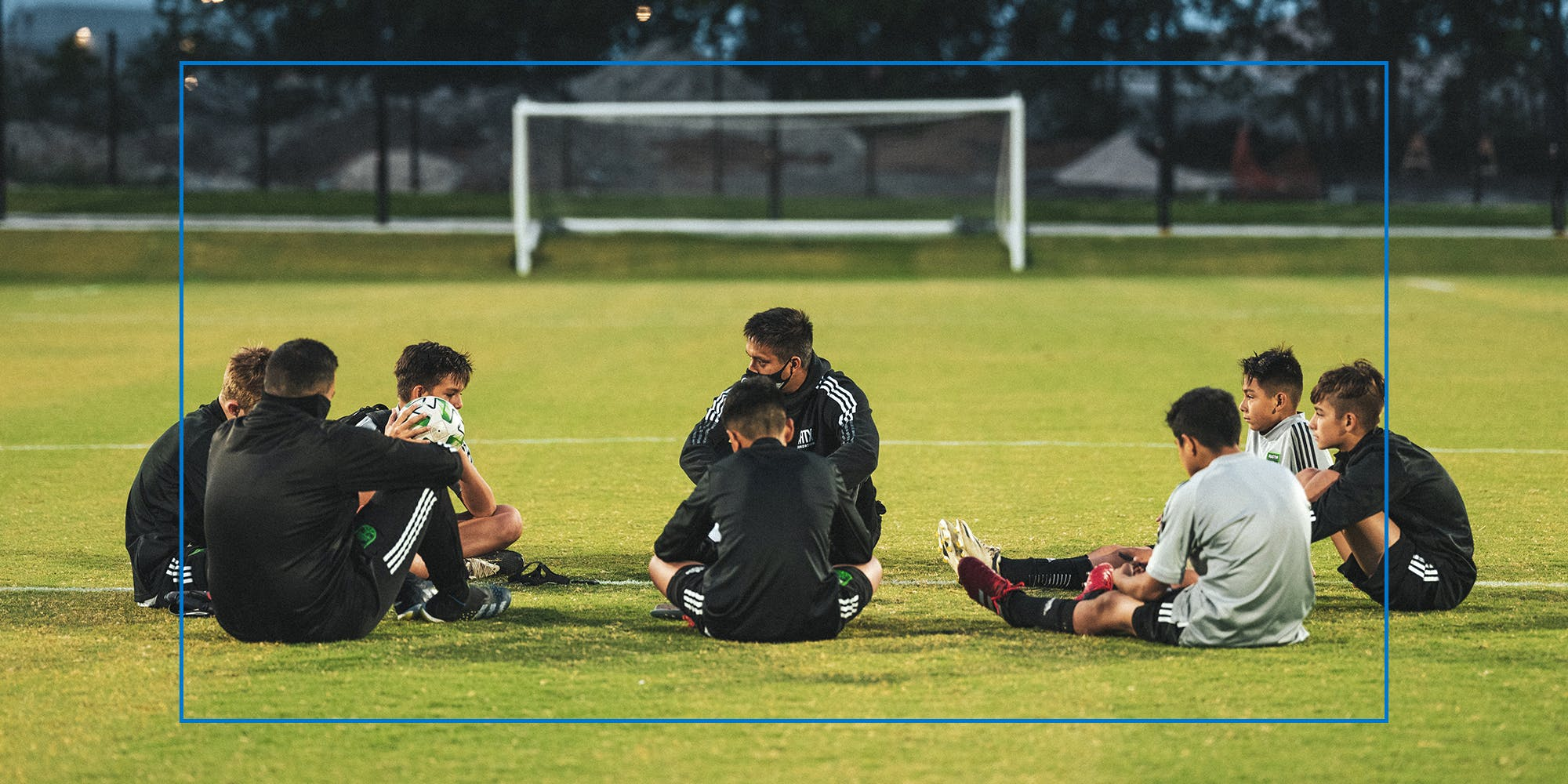 Soccer team sitting in circle on field