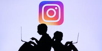 A silhouette of two children on laptops with the Instagram logo behind them.