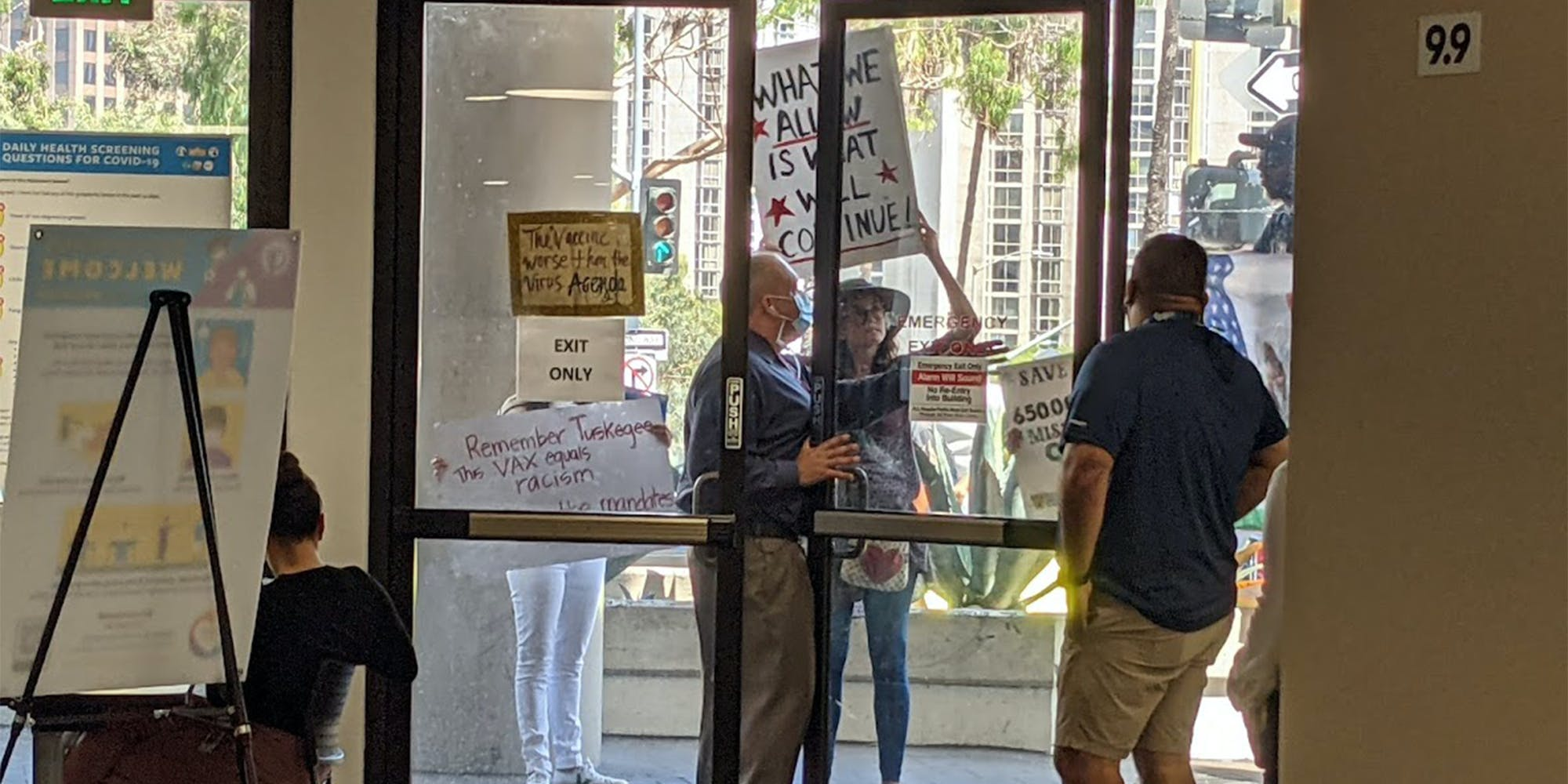 anti-vax protesters outside of glass doors