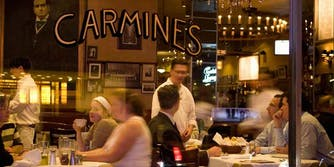 people eating in restaurant with CARMINE'S on glass window