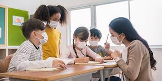 children at desks with teacher, all wearing facemasks