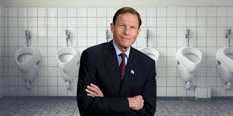 A man in front of urinals.