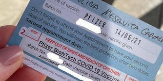 Hand holding vaccine card