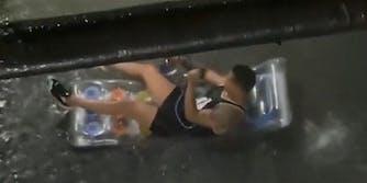 man smoking hookah on floatation device during flood
