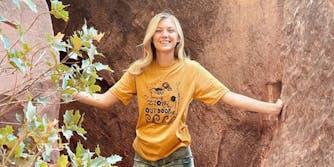 """Young woman wearing """"Zion outdoor"""" t-shirt between rocks"""
