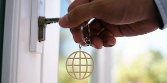 hand unlocks house using keychain of internet symbol