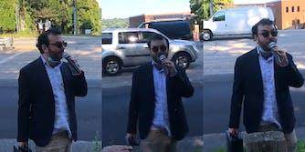 unkempt man in sports jacket with untucked shirt speaks into microphone on sidewalk