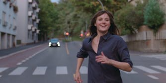 woman running in the middle of a street