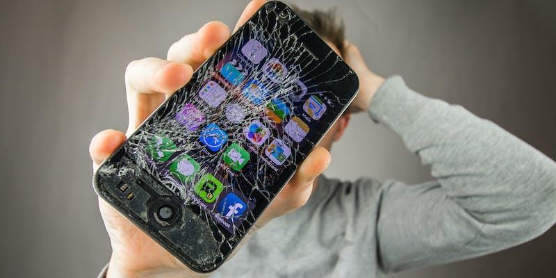 man holding smashed iphone