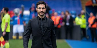 man in black suit walking on to a soccer pitch