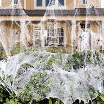bush covered in fake spider webs and hundreds of fake spiders