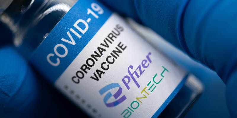 Covid-19 vaccine with Pfizer logo. Doctor's hand holds a bottle with a coronavirus vaccine on a white background.