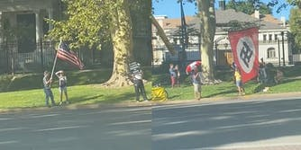A Nazi flag is seen by the road alongside people protesting the COVID-19 vaccine