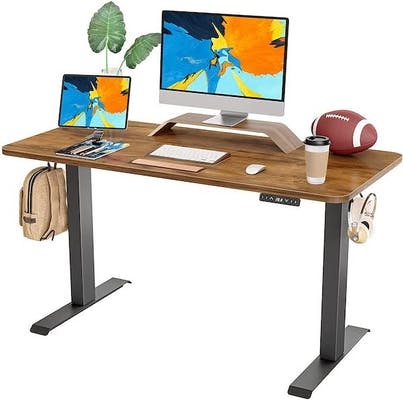 Wood raising desk with two computer monitors, a football, coffe, keyboard, and other knicknacks on the surface