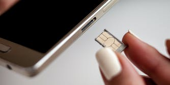 A person replacing a SIM card on a cell phone.