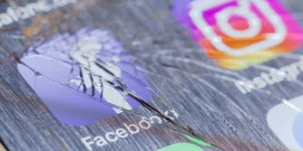 The Facebook and Instagram logos on a cracked phone. Symbolizing the apps being down.