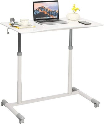 White raised standing desk with computer, lamp, mug, phone, and writing utensils on the surface. The perfect starter desk for a home office setup