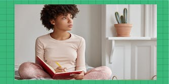 Cropped shot of dark skinned woman sits crossed legs, wears pyjamas, makes notes in diary, focused aside, blank copy space against domestic interior. Blogger creats publication for blog in notebook