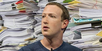 Mark Zuckerberg in front of a pile of memos, papers, and folders