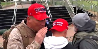 Man in Trump hat whispering to man in Make America Great Again hat