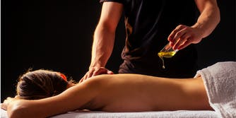 young indian woman lying on the table and getting ayurvedic massage with organic oil or honeyed in dark room.massagist male pouring out client back
