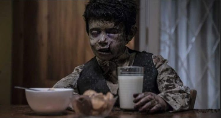 shudder - terrified, a dead boy sits at a table in front of a glass of milk, hiw body clearly rotting after time in the grave