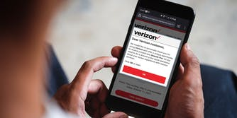 Person holding phone with Verizon scam text displayed on screen