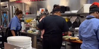 woman holding baby while she works in restaurant
