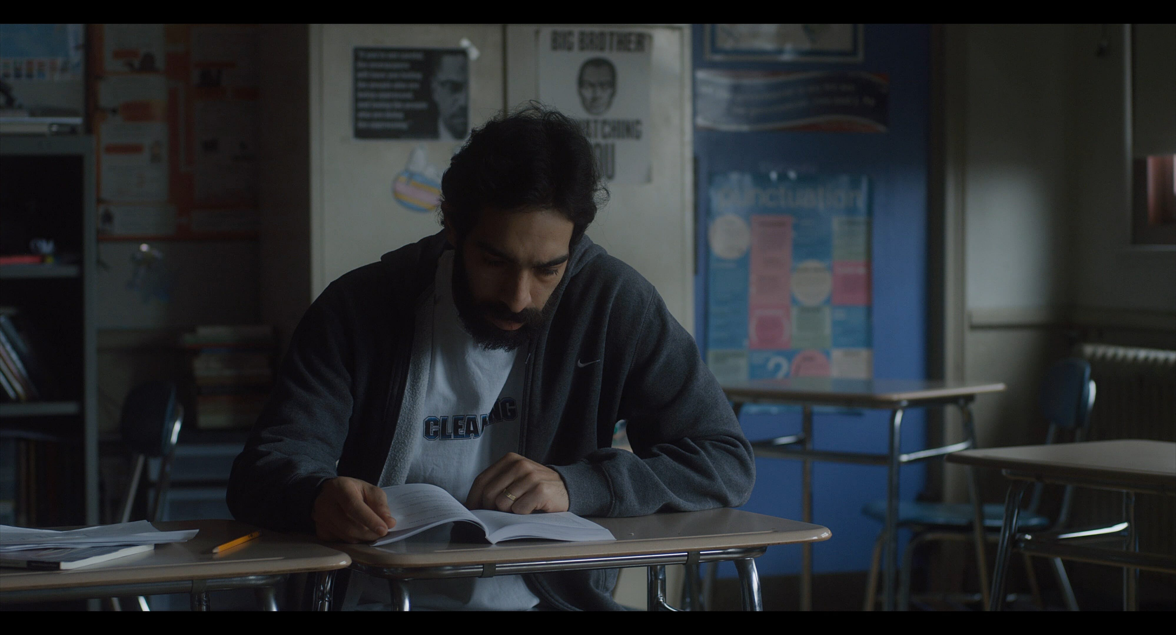 A man learns English in an empty, dark classroom in the film 'Carro.'