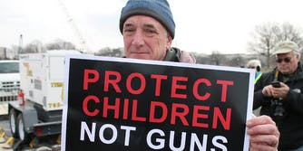 Man holding sign that says Protect Children Not Guns