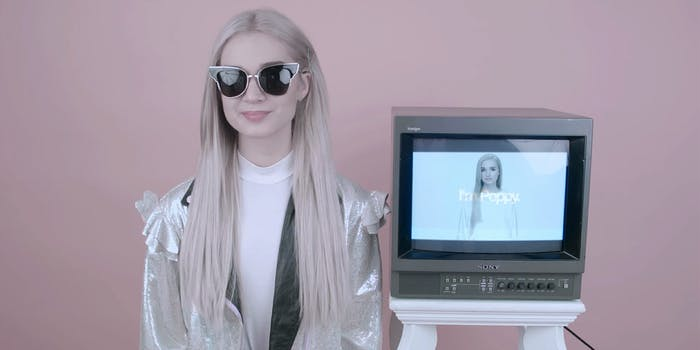 Poppy standing next to television showing Poppy