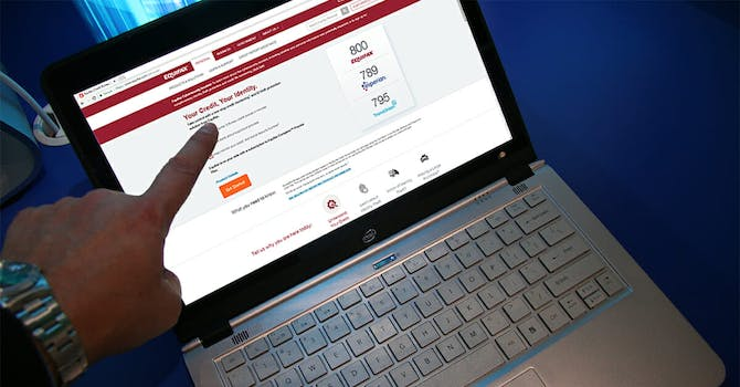 Man pointing at Equifax website on laptop