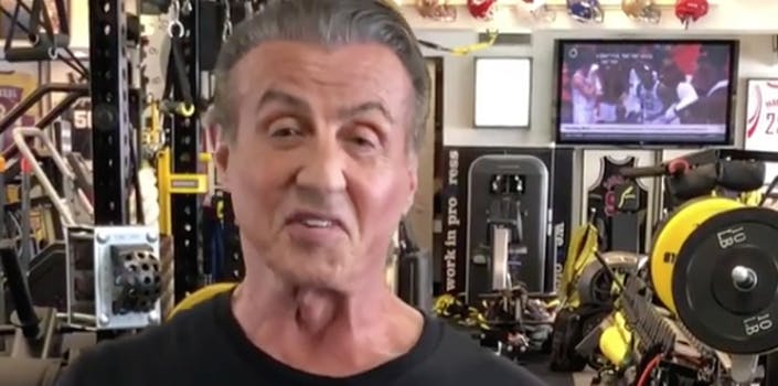 Sylvester Stallone smiles in front of some weight lifting equipment