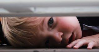 Toddler peeking under bed