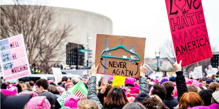 """A sign from 2017's Women's March on Washington pointing to a hanger and saying """"Never Again."""""""