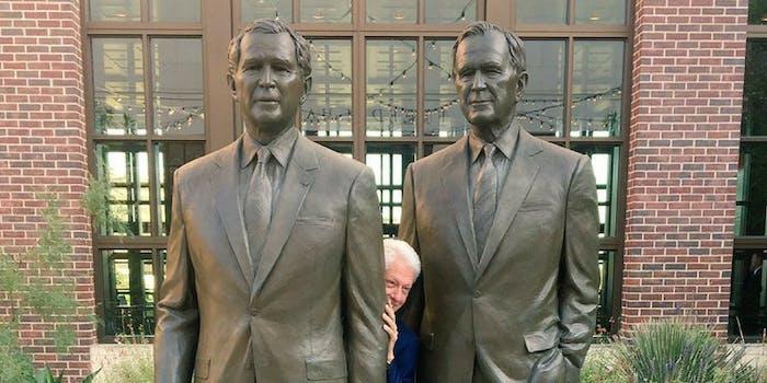 Bill Clinton hiding between statues of the Presidents Bush