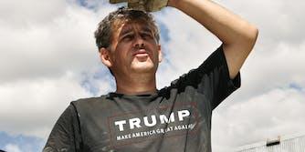 Man in Trump MAGA shirt shields eyes from sun