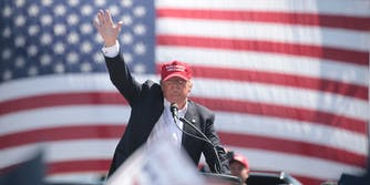 Donald Trump waving in front of American flag