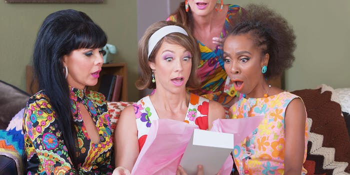 Shocked women looking in box at party