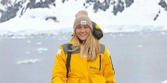 Cassie De Pecol, the first woman and fastest person to visit every country in the world, dressed in a yellow jacket and beanie near Paradise Island in Antarctica.