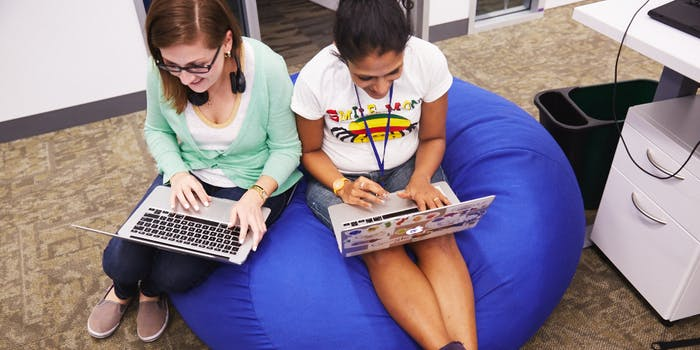 Googlers at work, two women working on laptops on a beanbag chair