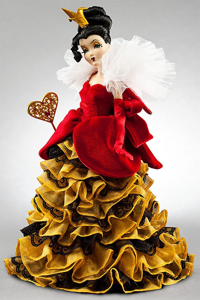 iimage of Queen of Hearts, Disney villains doll collection, showing a pretty, elegant woman clad in a red velvet dress with rich dark gold ruching on the skirt. She holds a gold wand with a large heart on the end, and has a small gold crown as in the movie Alice in Wonderland, but otherwise bears no resemblance to the Queen from the film.