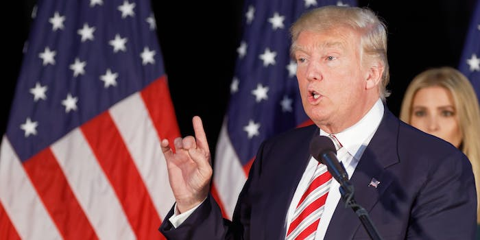Donald Trump Holding Up Index Finger in front of American Flags